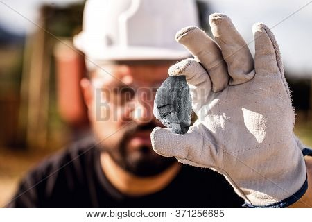 Crude Nugget Of Silver Stone, Manganese Or Palladium. Mining Man Holding Ore In His Hands. Spot Focu