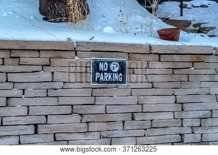 No Parking Sign On A Stone Brick Retaining Wall Topped With Snow In Winter
