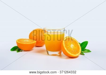 Orange Juice And Two Orange Slices And Green Leaves Isolated On White Background. Glass Of Orange Ju