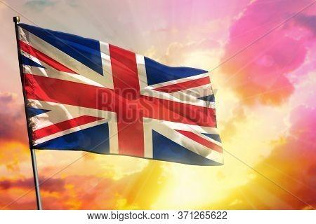 Fluttering United Kingdom (uk) Flag On Beautiful Colorful Sunset Or Sunrise Background. United Kingd