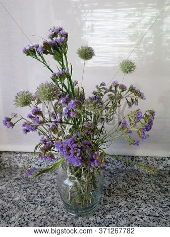 Blue Dried Wild Flowers In Glass Vase On Marble Worktop In Andalusian Kitchen