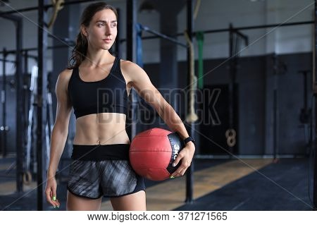 Muscular Strong Woman Carrying Medicine Ball At Crossfit Gym.