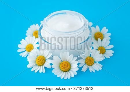 Face Cream In Bottle On A Blue Background, Skin Care Concept. Chamomile Flower And Glass Jar Of Mois