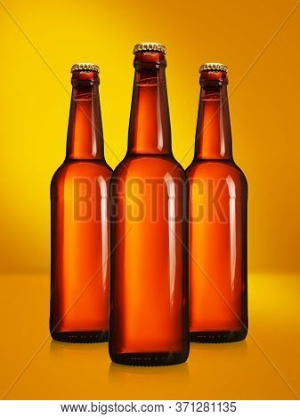 Brown Beer Bottles With Long Neck On Yellow Background. Mock-up Design Presentation.