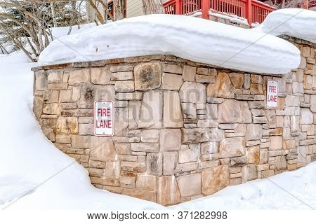 Stone Retaining Wall With Fire Lane Sign On A Hill With Thick Snow In Winter