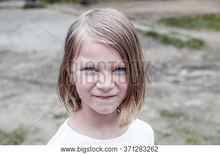 A Seven-year-old Girl With Unkempt Hair Looks Defiantly At The Camera