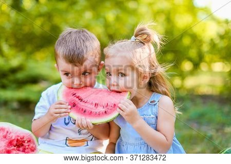 Two Kids Eating One Slice Of Watermelon In The Garden. Kids Eat Fruit Outdoors. Healthy Snack For Ch