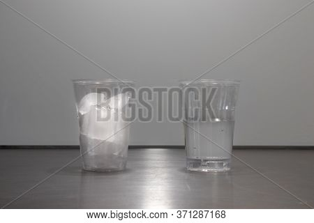Ice Cubes Melting In Glass Or Plastic Cup Showing Change In Physical State Of Water From Ice To Liqu