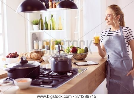 Attractive Woman Holding A Glass Of Orange Juice While Standing In The Kitchen