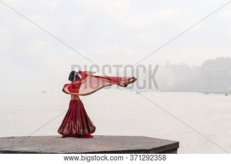A Beautiful Indian Woman In A Red Sari, Dancing With A Handkerchief In Her Hands, Alone On The Stree