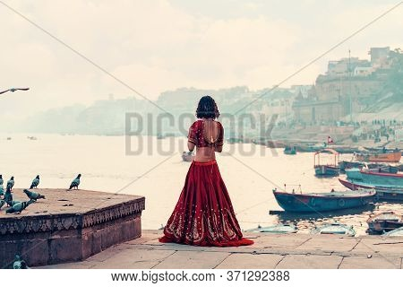 A Beautiful Indian Woman In A Red Sari Stands Alone On The Street. There Is A Flock Of Pigeons On Th