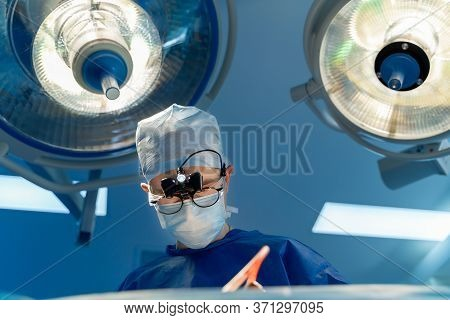 Portrait Of A Doctor Or Medical Specialist. Horizontal Portrait. Man In Scrubs. Lights Over Head. Ne