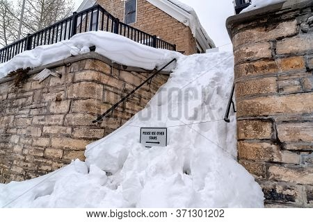 Snowed In Stairs Amid Stone Retaining Wall With Home And Cloudy Sky Background