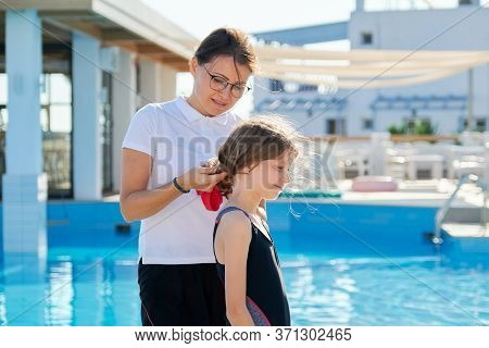 Family, Sport, Swimming, Health, Lifestyle Concept. Mom Helps Daughter Child Wear A Swimming Cap, Ou