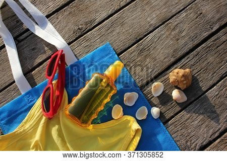 Summer Accessories: Sunscreen Spray Lotion, Yellow Tank Top, Sun Glasses, Blue Beach Bag And Seashel