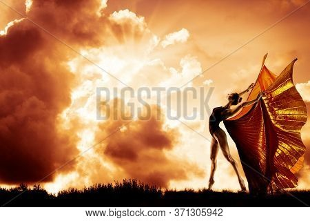 Woman Dance In Wings Costume Flying Over Sunset Sky, Beautiful Girl Dancing In Sun Rays Over Clouds