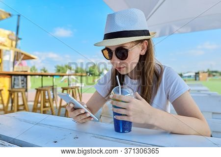 Teens, Lifestyle, Summer, Vacation. Teen Girl Making A Video Call On A Smartphone Sitting At A Table