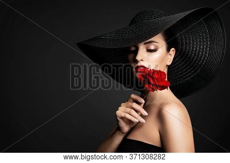 Beautiful Woman And Red Flower, Elegant Lady In Black Wide Broad Brim Hat Smelling Rose