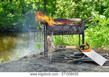Camping Trip With A Halt For Lunch Near The River. Bonfire In A Folding Grill. Near The Grill Lies A