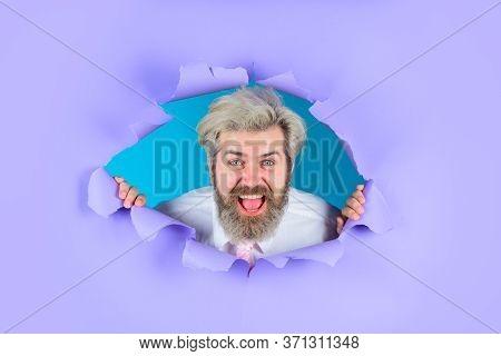 Business. Advertising. Through Paper. Bearded Man Looking Through Paper. Copy Space For Advertising.