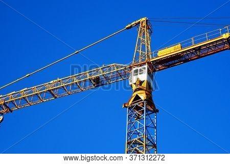Crane. Self-erection Crane Against Blue Sky. Construction Site.