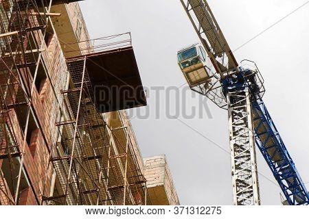 Crane. Self-erection Crane Near Concrete Building. Construction Site.