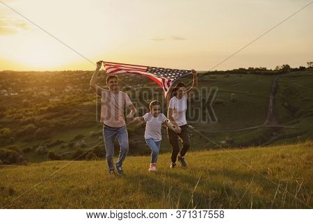 Happy Family With Usa Flag Runs On Nature In The Evening At Sunset. Mother Father And Daughter Celeb