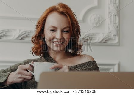 Horizontal Shot Of Pretty Redhaired Woman Watches Training Webinar On Laptop Computer, Drinks Refres