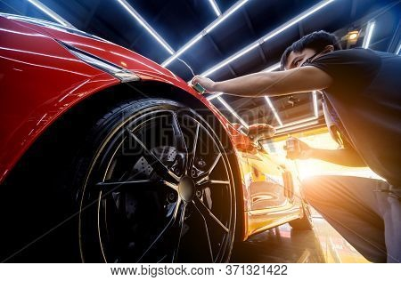 Car Service Worker Applying Nano Coating On A Car Detail