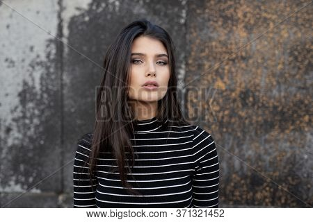 Frontal Portrait Of A Graceful Girl With Brunette Hair, In Casual Clothes, With Makeup, Supported By