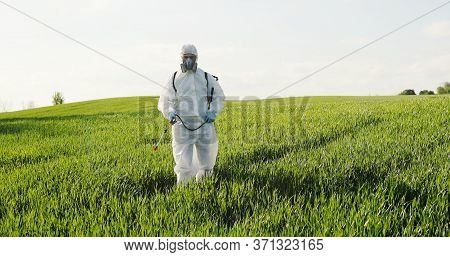 Caucasian Male Farmer In White Protective Costume, Mask And Goggles Walking The Green Field And Spra
