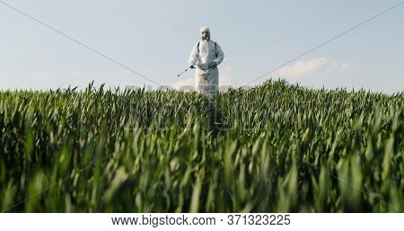 View From Below On Caucasian Male Farmer In White Protective Costume, Mask And Goggles Walking The G