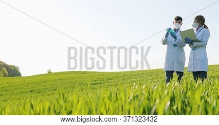 Caucasian Female And Male Harvest Researchers Holding Test Tube With Chemicals Pesticides And Laptop