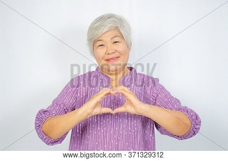 Love And Old People Concept -  Happy Senior Woman Showing Hand Heart Gesture And Smiling, Take Care