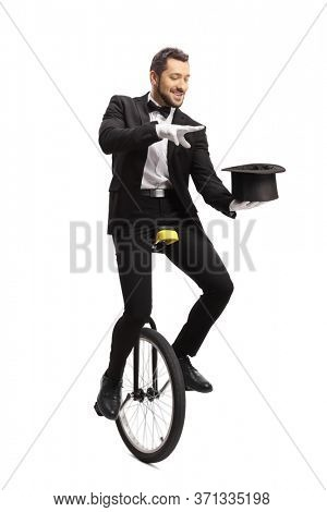 Magician riding a unicycle and performing a magic trick with a hat isolated on white background