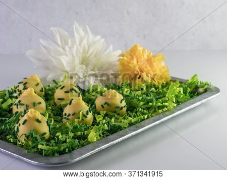 Rustic Metal Tray Filled With Green Paper Shreds And Yellow And Green Decorated Pineapple Upside Dow