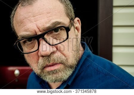 Incredulous adult man with glasses close-up face, outdoor portrait
