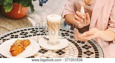 Closeup Stylish Girl Use Antibacterial Antiseptic Gel On Hand, Drink Coffee In French Outdoor Cafe.