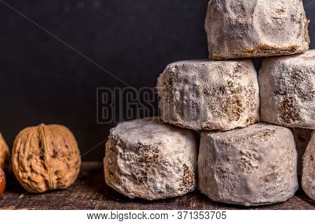 French Cheese Crottin De Chavignol With Hazelnut In The Dark Background. High Quality Photo