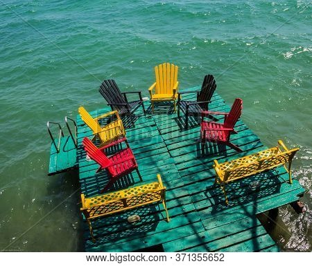 Multi-colored Adirondack Chairs And 2 Yellow Benches In Semi-circle On Green Deck In Havana, Cuba