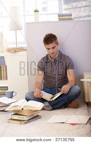 Student Studium zu Hause, sitzen auf Boden mit Büchern und Noten, Musik über Kopfhörer hören.