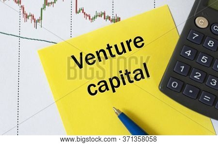 Venture Capital Words On Yellow Sheet On Table With Pen, Calculator And Graph. Business And Finance