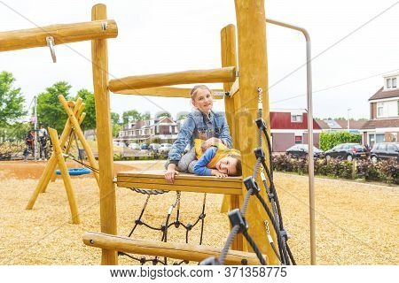 Selective Focus. The Children Climbing And Sliding On Slide In The Playground. Happy Children Playin