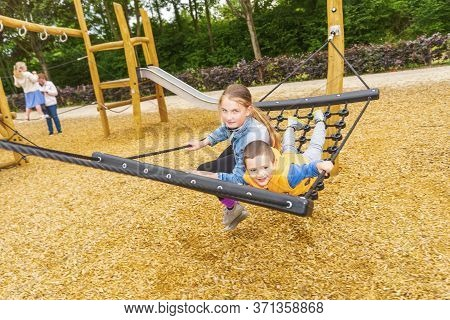 Tselective Focus. He Children Climbing And Sliding On Slide In The Playground. Happy Children Playin