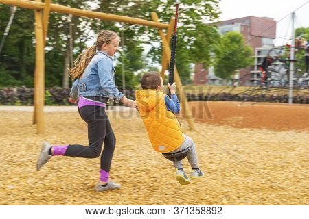 The Girl Climbing And Sliding On Slide In The Playground. Happy Children Playing And Having Fun At P