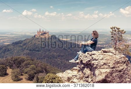 Young Woman Sits On Cliff Near Hohenzollern Castle, Germany. This Gothic Castle Is Landmark In Stutt