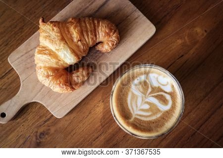 A Cup Of Coffee With Latte Art On Top And Butter  Croissant On Table, Top View