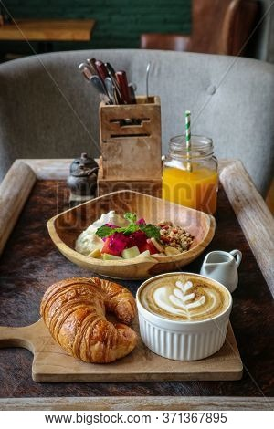 A Cup Of Coffee With Latte Art On Top, Butter  Croissant And Granola With Fresh Tropical Fruits And