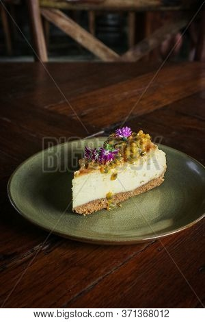 Slice Of Cheesecake With Passion Fruit On Round Plate On Wooden Background Closeup