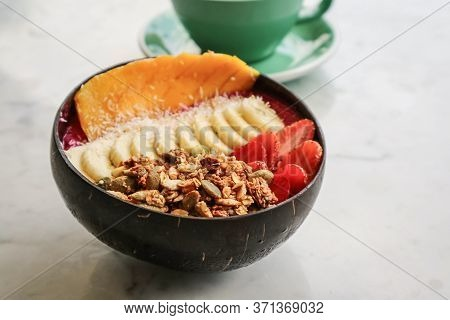 Smoothie Bowl With Strawberry, Dragon Fruit, Mango And Granola In Coconut N Bowl On White Table